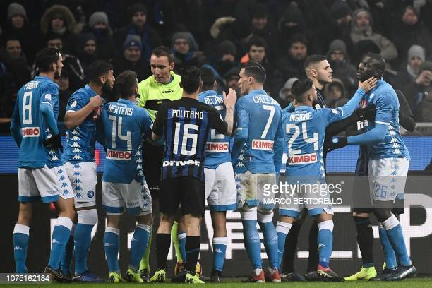 Napoli's Italian forward Lorenzo Insigne holds off Napoli's Senegalese defender Kalidou Koulibaly as referee Paolo Mazzoleni argues with Napoli's...