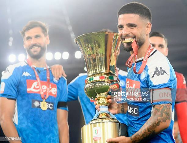 Napoli's Italian forward Lorenzo Insigne holds the trophy after Napoli won the TIM Italian Cup final football match Napoli vs Juventus on June 17...