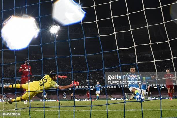 Napoli's Italian forward Lorenzo Insigne scores a last minute goal against Liverpool's Brazilian goalkeeper Alisson during the UEFA Champions League...