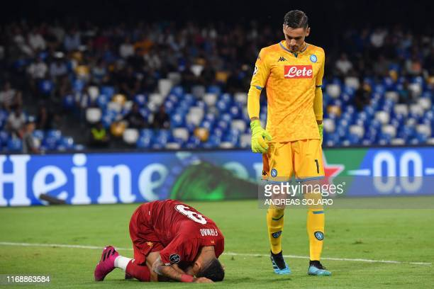 Napoli's Italian goalkeeper Alex Meret looks at Liverpool's Brazilian midfielder Roberto Firmino during the UEFA Champions League Group E football...