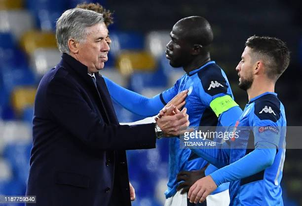 TOPSHOT Napoli's Italian head coach Carlo Ancelotti congratulates Napoli's Belgian forward Dries Mertens at the end of the UEFA Champions League...