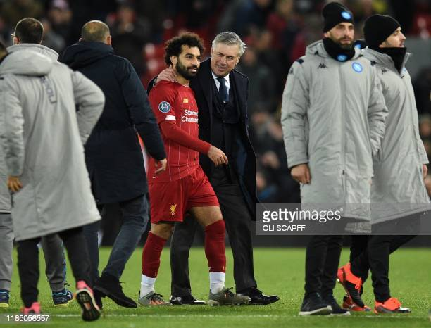 Napoli's Italian head coach Carlo Ancelotti leaves the pitch with Liverpool's Egyptian midfielder Mohamed Salah following the UEFA Champions league...