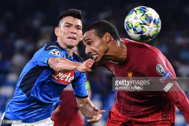 Napoli's Mexican forward Hirving Lozano and Liverpool's German-born Cameroonian defender Joel Matip go for the ball during the UEFA Champions League...