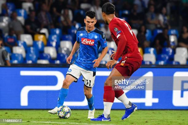 Napoli's Mexican forward Hirving Lozano challenges Liverpool's Dutch defender Virgil van Dijk during the UEFA Champions League Group E football match...