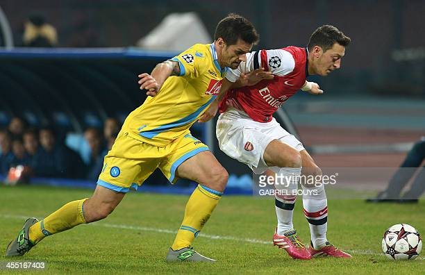 Napoli's midfielder Christian Maggio vies with Arsenal's German midfielder Mesut Ozil during the UEFA Champions League group F football match between...