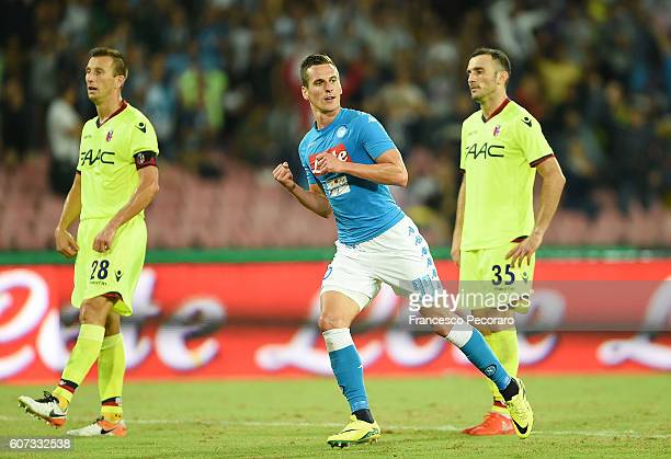 Napolis player Arkadiusz Milik celebrates after scoring the 31 goal beside the disappointment of Vasilis Torosidis and Daniele Gastaldello of Bologna...