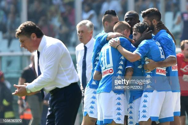 Napoli's players celebrate teammate Lorenzo Insigne's goal with coach Carlo Ancelotti as Torinos' coach Walter Mazzarri reacts during the Italian...
