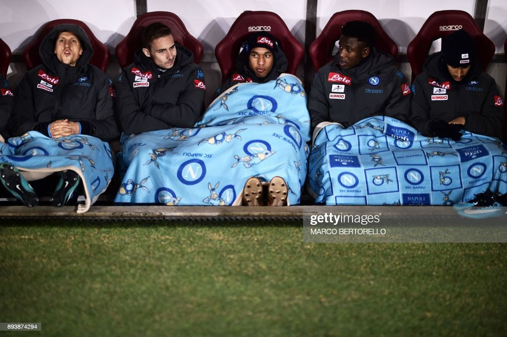 TOPSHOT - Napoli's players cover themselves with blankets on the bench prior the Italian Serie A football match Torino Vs Napoli on December 16, 2017 at the 'Grande Torino' stadium in Turin. /