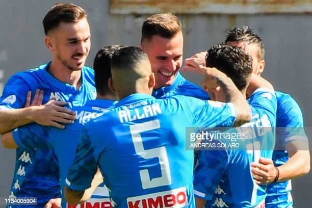 Napoli's Polish forward Arkadiusz Milik celebrates with teammates after opening the scoring during the Italian Serie A football match AS Roma vs SSC...
