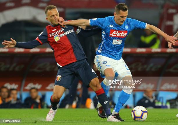 Napoli's Polish forward Arkadiusz Milik holds off Genoa's Italian defender Domenico Criscito during the Italian Serie A football match Napoli vs...