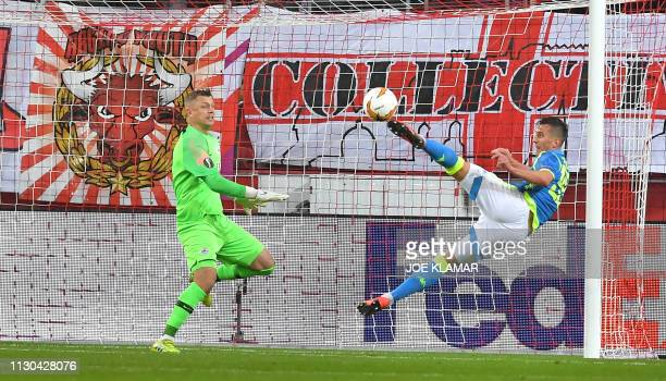 Napoli's Polish forward Arkadiusz Milik scores the opening goal past Salzburg's German goalkeeper Alexander Walke during the UEFA Europa League last...