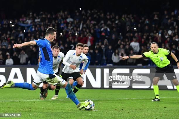 Napoli's Polish forward Arkadiusz Milik shoots a penalty to score his third goal during the UEFA Champions League Group E football match Napoli vs...