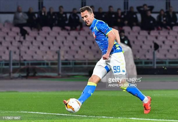 Napoli's Polish forward Arkadiusz Milik shoots to open the scoring during the UEFA Europa League round of 16 first leg football match Napoli vs...