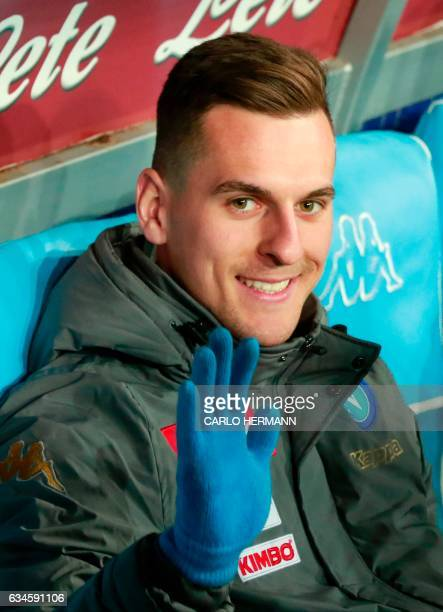 Napoli's Polish forward Arkadiusz Milik waves as he seats on the bench prior to the Italian Serie A football match SSC Napoli vs Genoa CFC on...