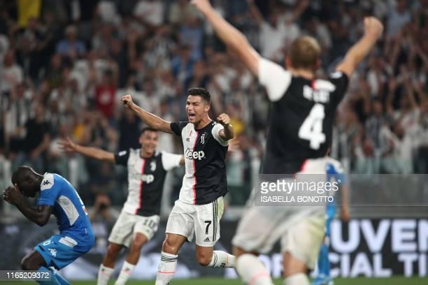 Napoli's Senegalese defender Kalidou Koulibaly reacts after scoring an own goal while Juventus' Portuguese forward Cristiano Ronaldo celebrates...