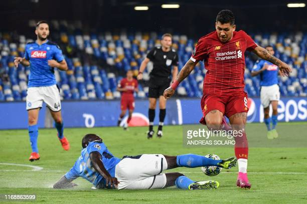 Napoli's Senegalese defender Kalidou Koulibaly tackles Liverpool's Brazilian midfielder Roberto Firmino during the UEFA Champions League Group E...