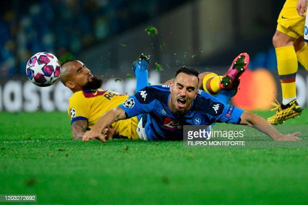 Napoli's Serbian defender Nikola Maksimovic and Barcelona's Chilean midfielder Arturo Vidal fall during the UEFA Champions League round of 16...