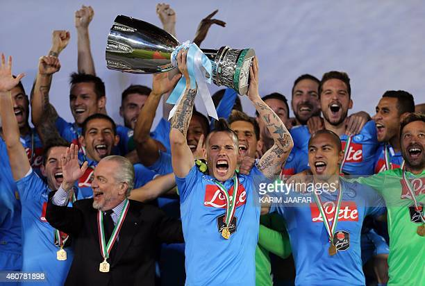 Napoli's Slovak midfielder and captain Marek Hamsik lifts the Italian Super Cup trophy following their football match against Serie A champions...