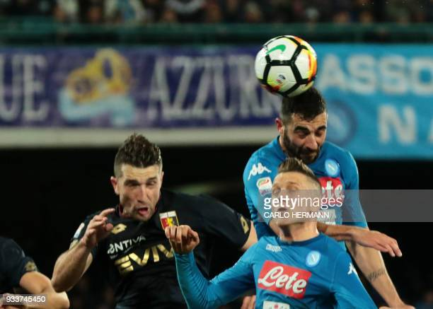 Napoli's Spanish defender Raul Albiol heads the ball and scores during the Italian Serie A football match SSC Napoli vs Genoa CFC on March 18, 2018...