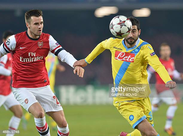 Napoli's Spanish defender Raul Albiol outpasses Arsenal's British defender Carl Jenkinson during the UEFA Champion's League group F football match...