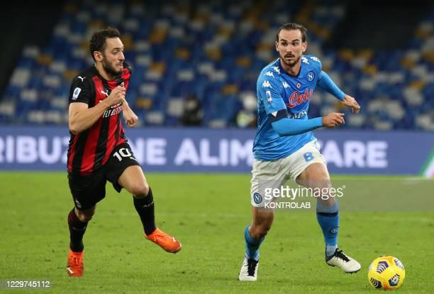 Napoli's Spanish midfielder Fabian Ruiz fights for the ball with AC Milan's Turkish midfielder Hakan Calhanoglu during the Serie A football match SSC...