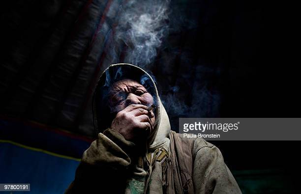 Narambat smokes cigarette keeping warm after working long hours at the garbage dump on March 12 2010 in Ulaan Baatar Mongolia Narambat and his family...