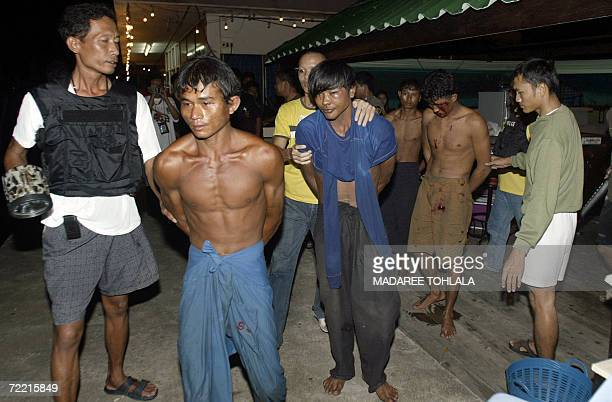 Thai security officers take away handcuffed Myanmar workers from a fishing boat after a murder incident in Thailand's southern Narathiwat province 16...