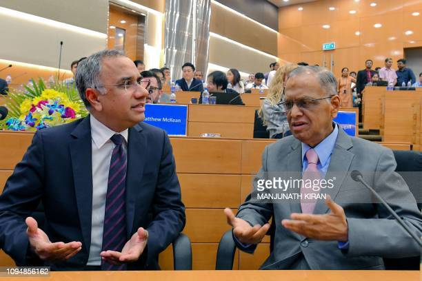 Narayana Murthy, founder of Indian technology company Infosys , and Managing Director and CEO Salil Parikh gesture as they speak together prior to a...