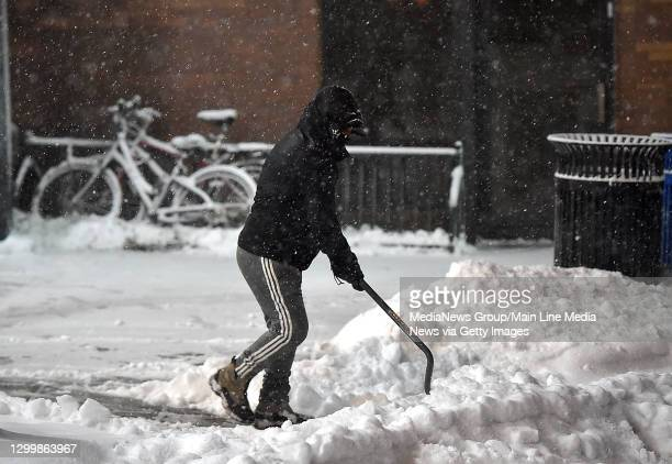 Narberth, PA> Feb. 1 :A person shovels snow at the Narberth train station Monday evening.