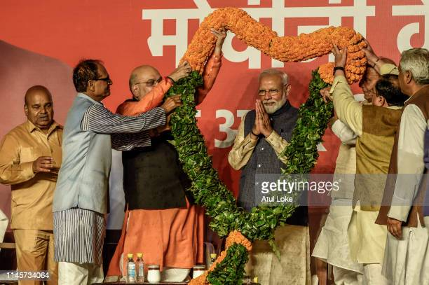 Narendra Modi acknowledges to the victorious party workers while getting garland at the BJP party head quarters in New Delhi, India. Indian Prime...