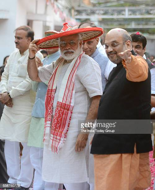 Narendra Modi being presented a traditional Assamese hat by BJP president Amit Shah during a celebration on Assam assembly polls victory in New Delhi