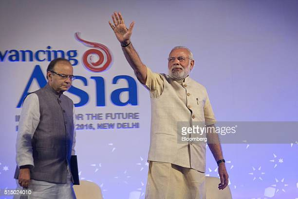 Narendra Modi India's prime minister center waves as he arrives on stage with Arun Jaitley India's finance minister at the Advancing Asia Conference...