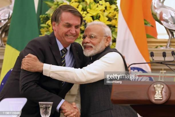 Narendra Modi, India's prime minister, right, embraces Jair Bolsonaro, Brazil's president, at Hyderabad House in New Delhi, India, on Saturday, Jan....