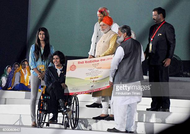 Narendra Modi Prime Minister of India gives a cheque of rupees four crore to Deepa Malik first Indian woman to win a medal in Paralympic during the...