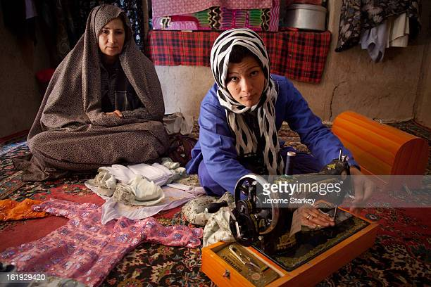 Narguz makes children's clothes with a sewing machine in her home in Herat , as a social worker looks on . The teenager was jailed for adultery and...