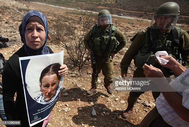 Nariman Tamimi holds a portrait of Rachel Corrie a US peace activist who was run over by an Israeli bulldozer during a demonstration in Gaza in 2003...