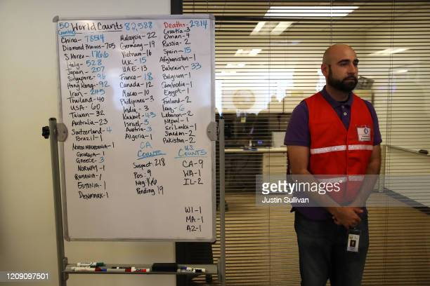 Narimon Mirza stands next a to a whiteboard showing the number of Coronavirus COVID19 cases around the world at the Medical Health and Coordination...