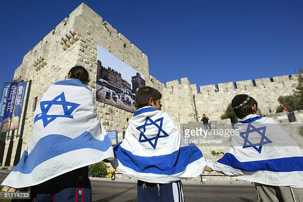 Narkiss Barki 13yearsold and her two younger brothers Dvir sixyearsold and Amir fiveyearsold from Jerusalem wear Israeli flags as they take part...