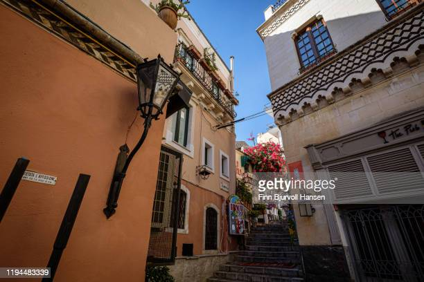 narow typical street and buildings in the old center of taormina, sicily, italy with flowers - finn bjurvoll stock pictures, royalty-free photos & images