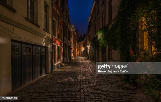 narrow alley along buildings at night - narrow stock pictures, royalty-free photos & images