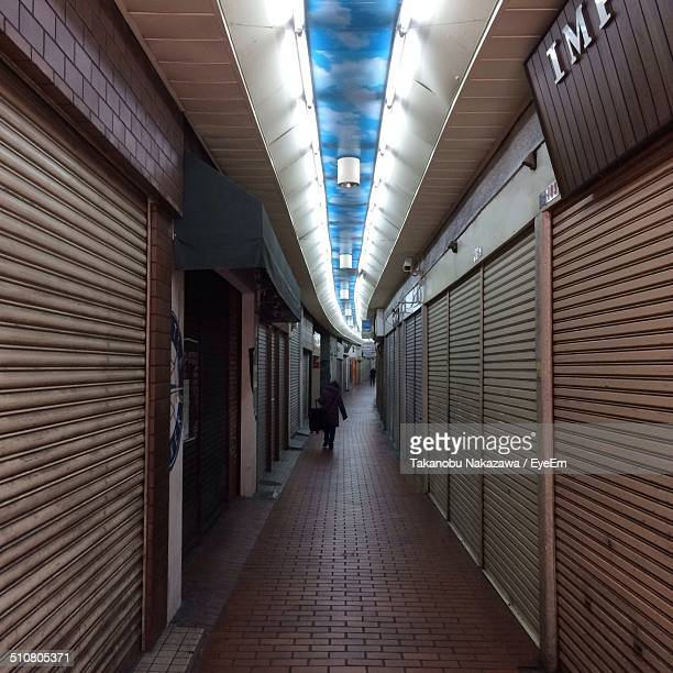 Narrow alley along built structures with shutters down