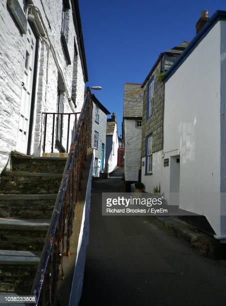 narrow alley amidst buildings against blue sky - port isaac stock pictures, royalty-free photos & images