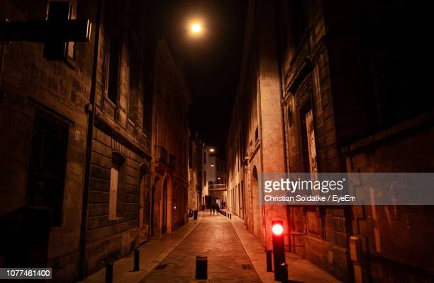 narrow alley amidst buildings in city at night - christian soldatke stock pictures, royalty-free photos & images