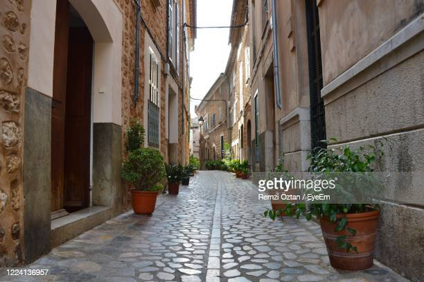 narrow alley amidst buildings in city. old town of sóller, majorca, spain - 中庭 ストックフォトと画像