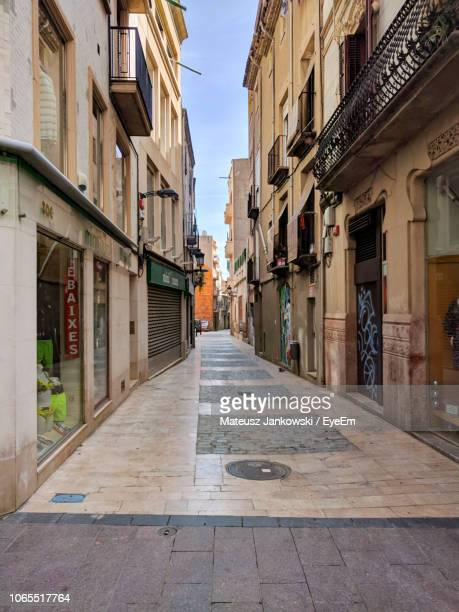 narrow alley amidst buildings in city - reus spain stock pictures, royalty-free photos & images