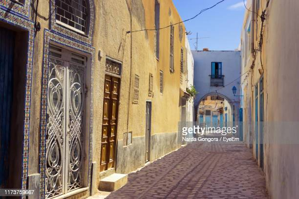 narrow alley amidst buildings in city - kairwan stock pictures, royalty-free photos & images