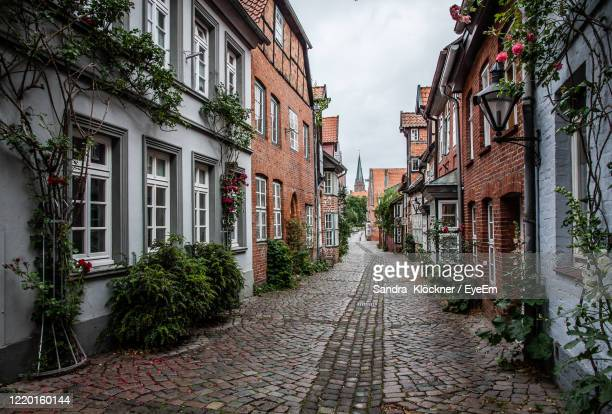 narrow alley amidst buildings in city - lüneburg stock pictures, royalty-free photos & images