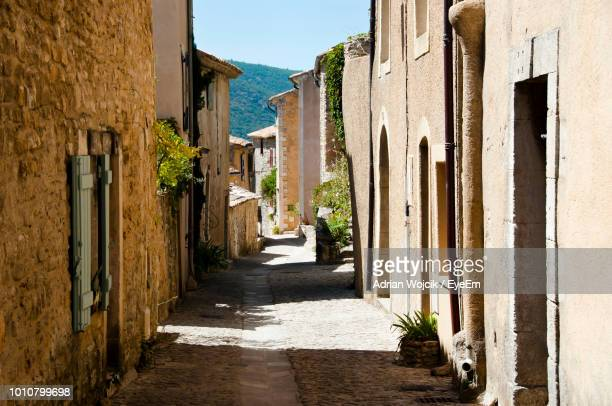 narrow alley amidst buildings in town - village photos et images de collection