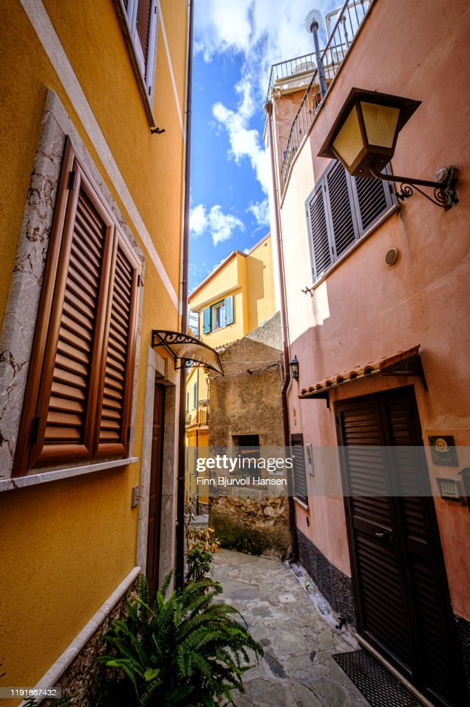 Castelmola, Taormina, Italy - November 8, 2019: Narrow alley and old houses with plants outside in Castelmola : Stock Photo