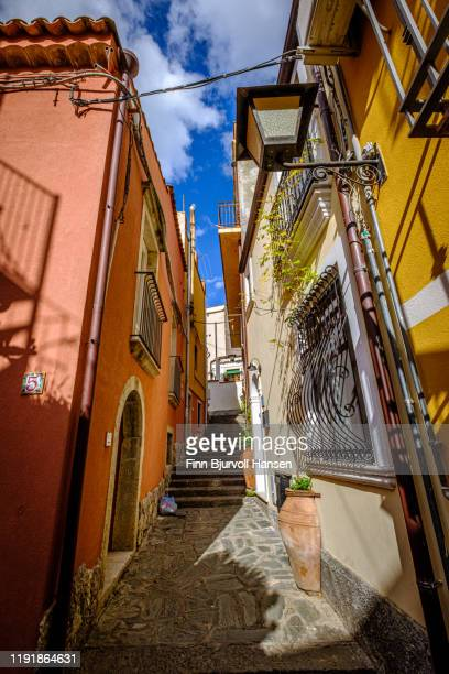 narrow alley and old houses with plants outside in castelmola taormina sicily italy - finn bjurvoll stock photos and pictures